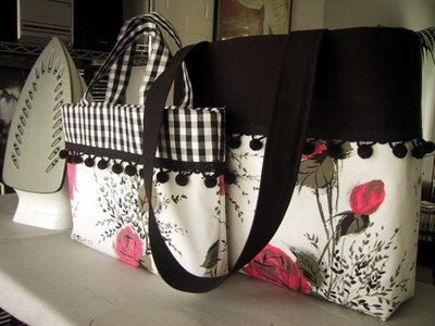 Two hand-made bags in colours of pink, white and black, displayed on an ironing board with an iron.