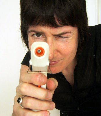 Woman holding a hot glue gun aiming at the camera.