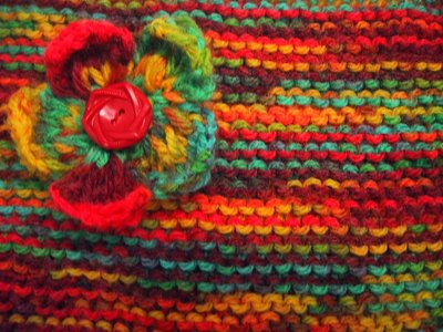 Multi-coloured garter stitch knitting, with a knitted flower made from the same wool with a button in the centre, pinned to it.